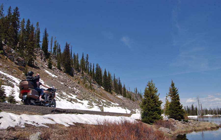 A motorcycle passes between the base of Talus Slope and the Lewis River in Yellowstone National Park. (Yellowstone Gate file photo/Ruffin Prevost - click to enlarge)