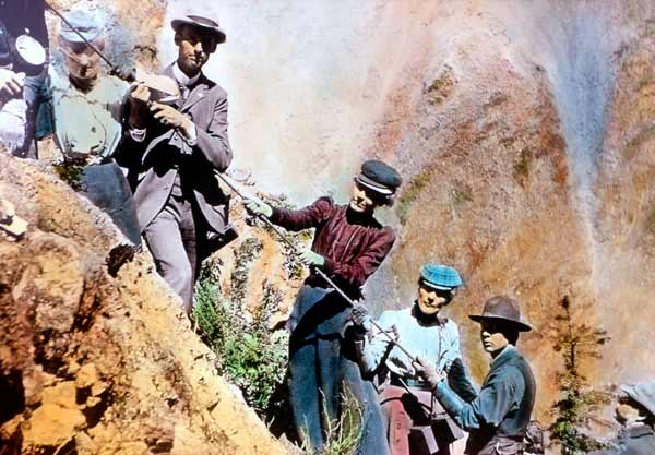 A colorized photo shows early Yellowstone National Park visitors climbing along Uncle Tom's Trail. (Yellowstone Digital Slide File)
