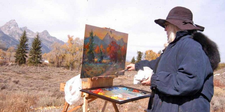 Idaho resident Elesa Shuman paints the Tetons amid fall colors as viewed from the Dornan's parking lot in Grand Teton National Park in this October 2012 file photo.