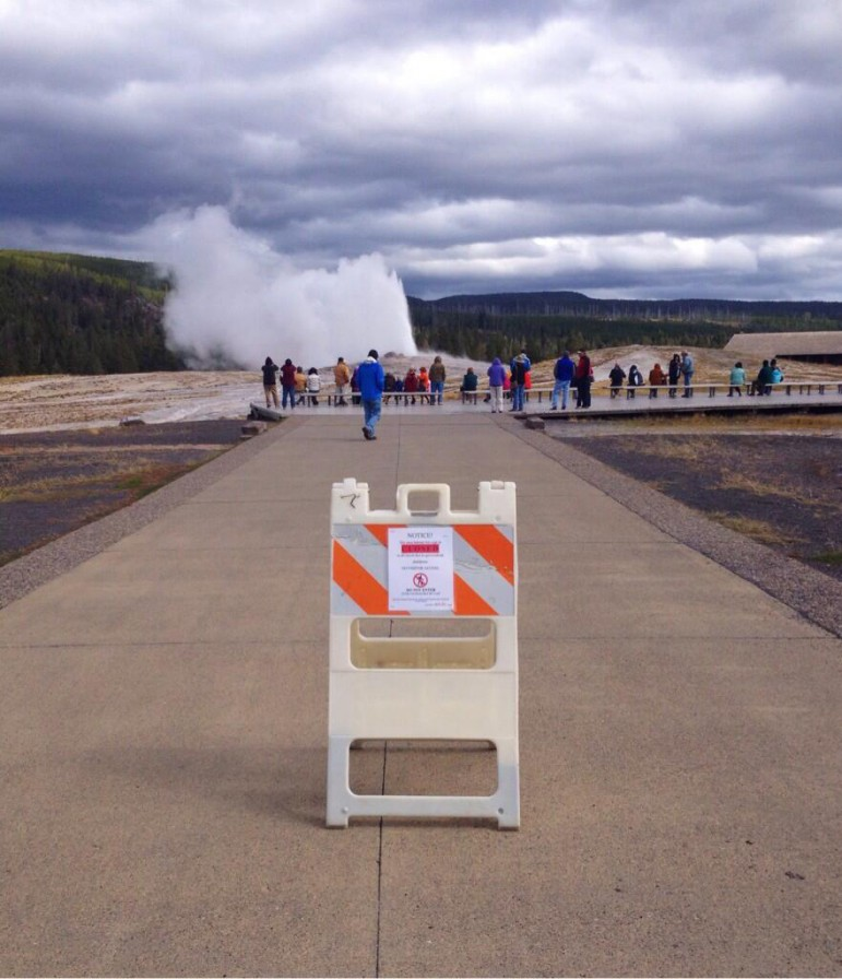 About two dozen visitors to Yellowstone National Park watch Old Faithful Geyser erupt Tuesday afternoon despite a sign advising that the attraction is closed in the wake of a federal goverment shutdown. No visitors were allowed into national parks Tuesday, while those already inside park boundaries will be asked to leave.