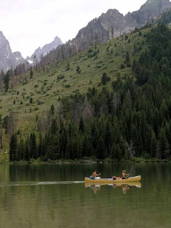 Boaters paddle a canoe on String Lake in Grand Teton National Park.