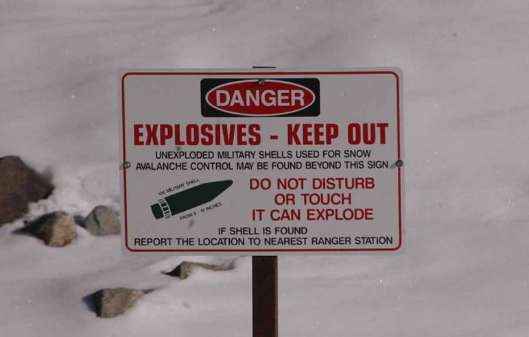 A sign atop Sylvan Pass in Yellowstone National Park warns of unexploded shells from a howitzer used for avalanche mitigation. (Ruffin Prevost/Yellowstone Gate)