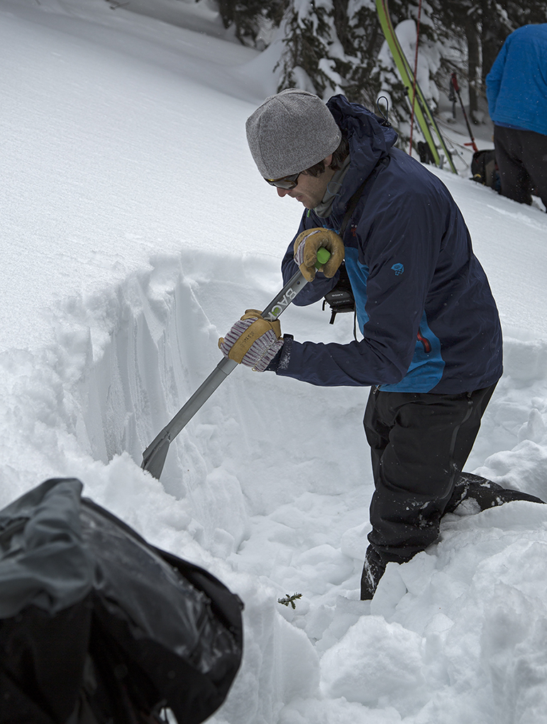 Instructor Clark Corey demonstrates the proper way to dig a snow pit to inspect conditions as part of avalanche forecasting.
