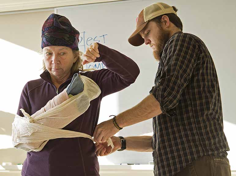 """Wilderness Medicine Institute instructor Tate Higgins demonstrates a """"sling and swath"""" on a student."""