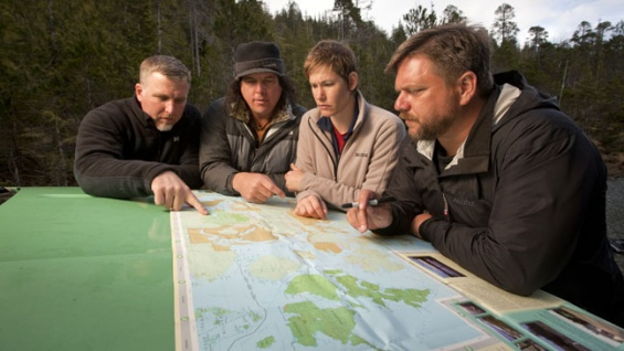 """From left, Cliff Barackman, James Fay, Ranae Holland and Matt Moneymaker consult a map during an episode of """"Finding Bigfoot."""""""