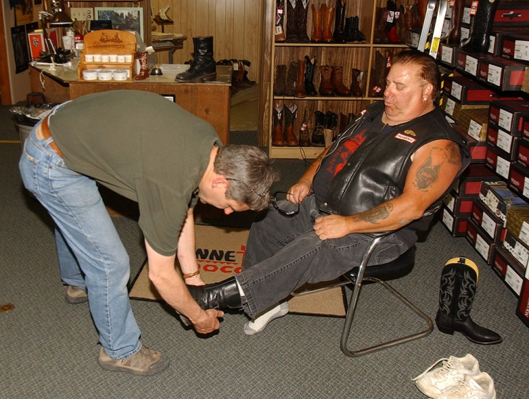 A member of the Hells Angels motorcycle club tries on footwear at Wayne's Boot Shop during the group's 2006 World Run in Cody, Wyo.