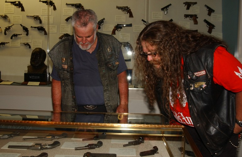 Two Hells Angels motorcycle club members from California survey a few of the thousands of firearms on display at the Cody Firearms Museum in the Buffalo Bill Center of the West during the group's 2006 World Run in Cody, Wyo.