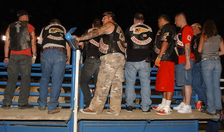 Members of the Hells Angels motorcycle club  and friends stand atop the bucking chutes  at the Cody Nite Rodeo during the group's 2006 World Run in Cody, Wyo.