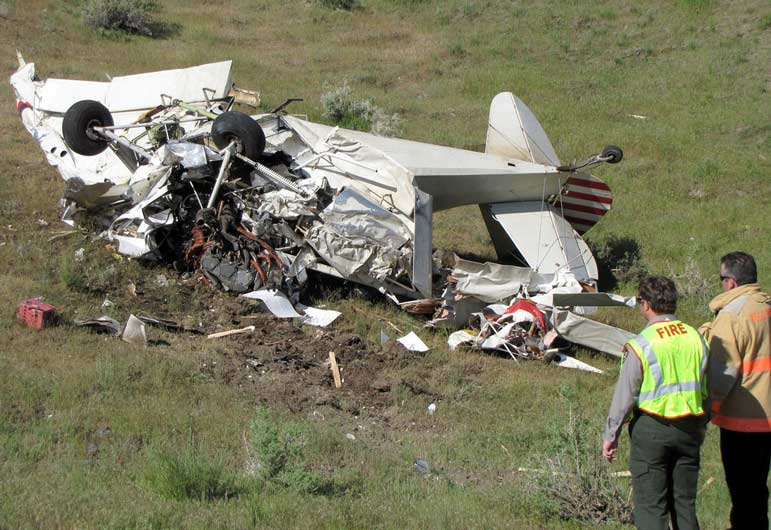Emergency responders view the wreckage of a small plan that crashed Monday in Yellowstone National Park.