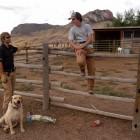 P.J. Schneider, left, and dog dexter take a break while installing an electric fence last month with Russ Talmo. Defenders of wildilfe helped Schneider with cost-sharing and tehnical expertise on the project at a ranch southwest of Cody, Wyo. where chickens and goats could attract grizzly bears.