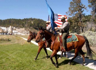 The Yellowstone National Park Mounted Color Guard passes in front of the Liberty Cap at Mammoth Hot Springs during a Sept. 3 naturalization ceremony for new citizens from four states