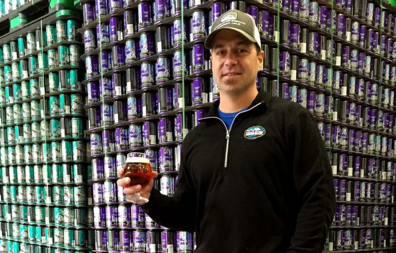 Derek Beardsley samples a Jenny Lake Lager in front of a stack of cans at the Snake River Brewery in Jackson, Wyo.