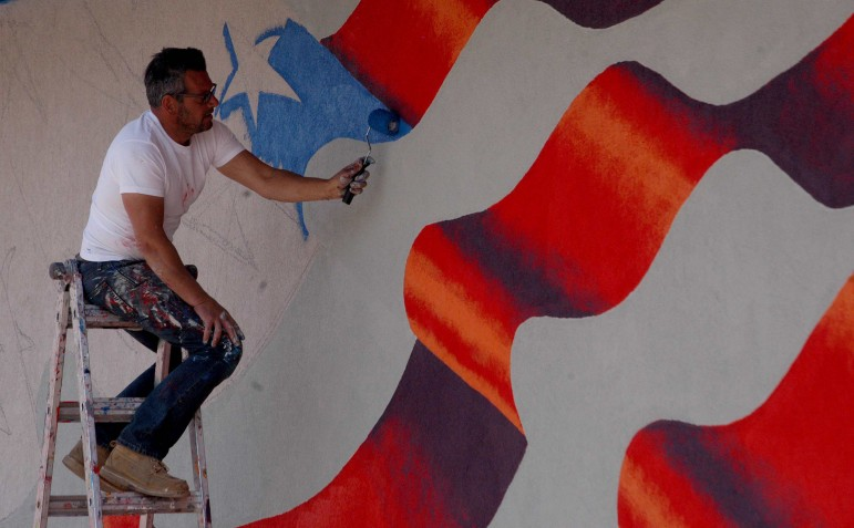Using just a paint roller, Scott LaBaido creates an American flag mural on the exterior wall of the Veterans of Foreign Wars building in Cody, Wyo.