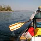 A canoeist paddles along the southeast arm of Yellowstone Lake in Yellowstone National Park.