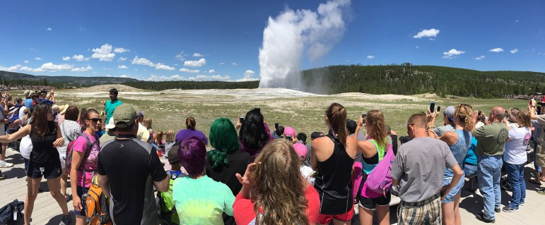 Visitors watch Old Faithful geyser erupt in Yellowstone National Park.