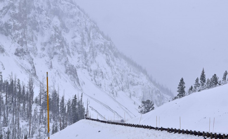 A car navigates the road leading up to Sylvan Pass on Tuesday afternoon after snowy conditions briefly closed the road between Cody, Wyo. and Fishing Bridge in Yellowstone National Park.