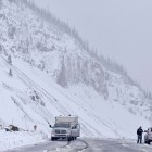 Two motorists pause at a pull-out atop Sylvan Pass to discuss snowy road conditions Tuesday in Yellowstone National Park.