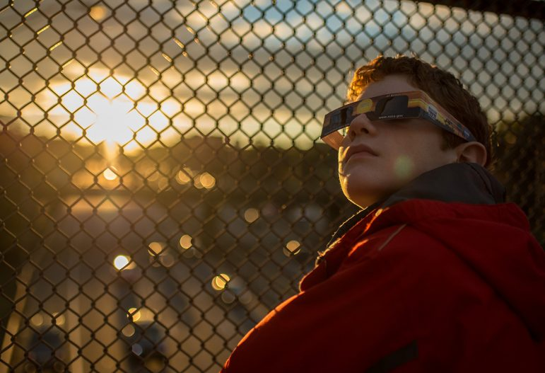Alex Frye, 12, checks his special viewing glasses prior to viewing the partial solar eclipse from a highway overpass in Arlington, VA, Thursday, Oct. 23, 2014. (Image: NASA)